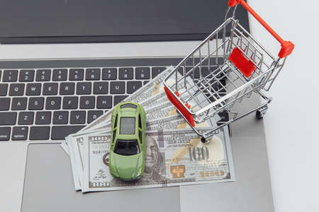 Toy car and shopping cart with dollar banknotes on a laptop. Online purchase car concept