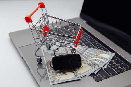 Car keys with dollar banknotes and shopping cart on keyboard. Online purchase car concept