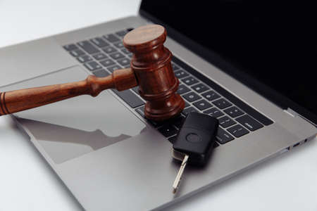 Judge gavel and car keys on laptop computer keyboard. Symbol of law, justice and online car auction.