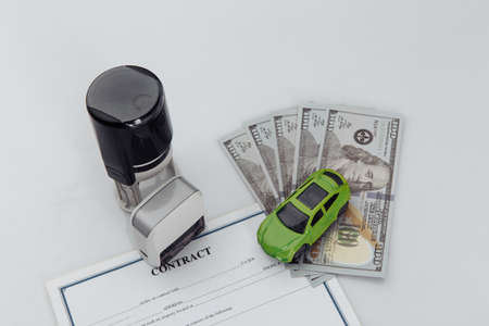 Purchase contract for a car with dollar banknotes, stamps and car keys on a white background
