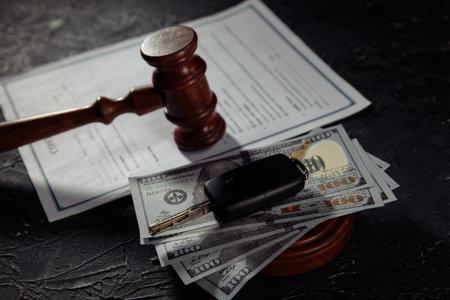 Car keys on dollar banknotes and wooden judge gavel close-up