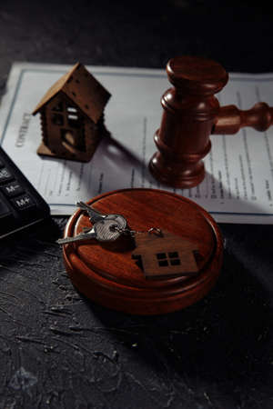 Judge gavel and house keys on gray table. Real estate law, house arrest concept. Vertical image 版權商用圖片