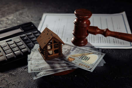House model on dollar banknotes and judges gavel on a table. Mortgage, bankruptcy or divorce concept 版權商用圖片
