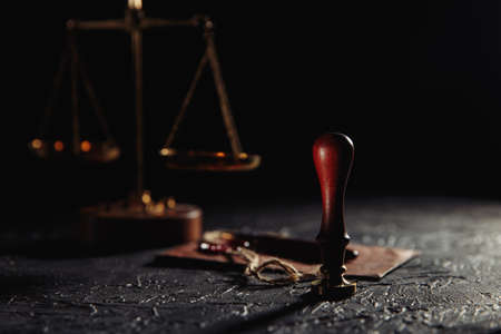 Law and justice concept. Scales of justice, brown envelope with seal and wooden stamp in a courtroom 版權商用圖片 - 162029213