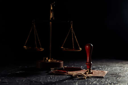 Law and justice concept. Notary tools. Scales of justice, envelope with seal and wooden stamp in a dark courtroom