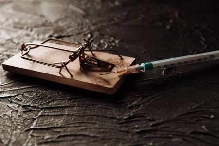 Mousetrap with a bait in the form of syringe close-up. Addiction and dependence on drugs