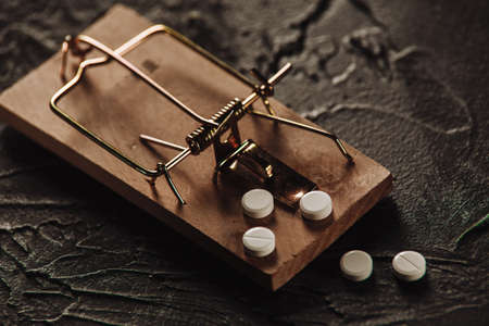 Mousetrap with a bait in the form of pills close-up. Addiction and dependence on drugs 版權商用圖片