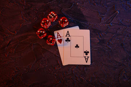 Online gambling theme. Aces and five red dices on a grey background