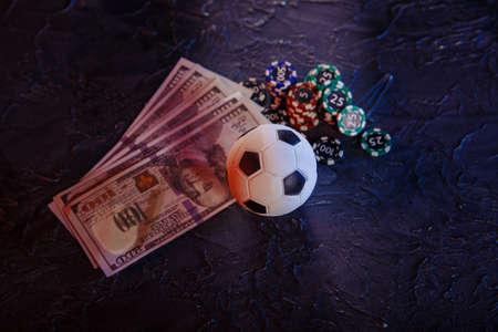 Gambling chips, soccer ball and dollar banknotes on a grey background. Gambling and betting concept