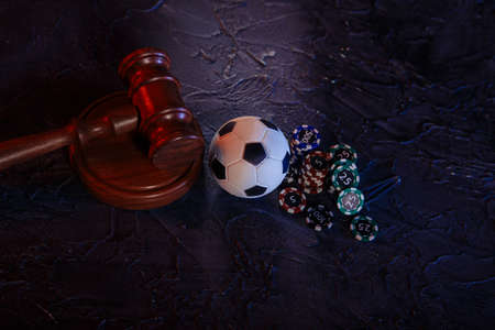 Online gambling and justice theme, soccer ball, playing chips and judge wooden gavel on a grey background 版權商用圖片