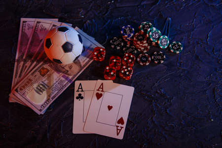 Gambling chips, cards and soccer ball on dollar banknotes. Online gambling and betting concept 版權商用圖片 - 162029283