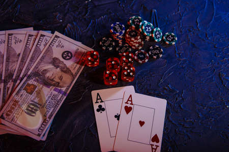 Game cards with chips and dices on a grey background. Poker online