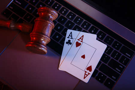 Law and rules for online casino concept, judge gavel and aces on keyboard of laptop 版權商用圖片