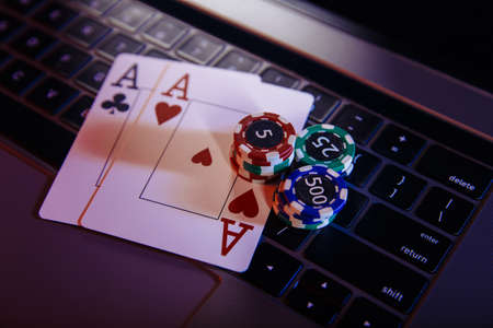 Online gambling theme. Aces with playing chips on a laptops keyboard close-up
