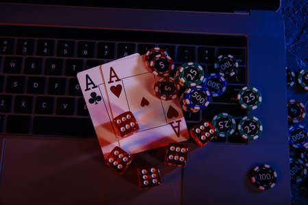Casino play online. Playing chips, cards and dices on laptops keyboard. Top view