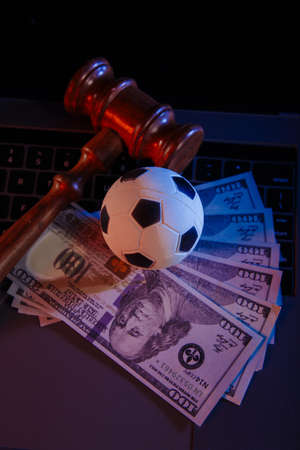 Soccer ball, money and wooden judge gavel on a laptop. Betting and law concept. Vertical image