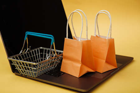 Concept of online shopping. Orange bags and shopping cart on keyboard 版權商用圖片 - 162029382
