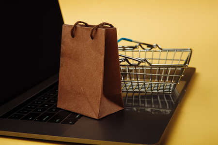 Concept of online shopping. Shopping bag and cart on keyboard