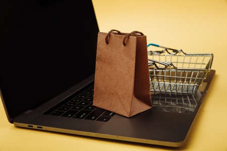 Concept of online shopping. Paper shopping bag and cart on keyboard of laptop