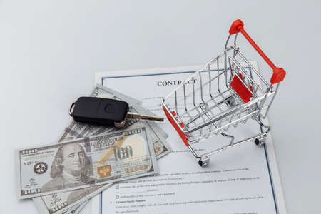 Car keys, money and shopping cart. Car sale or purchase concept