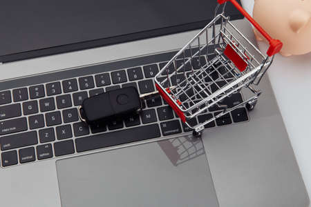 Car key and shopping trolley above laptop keyboard