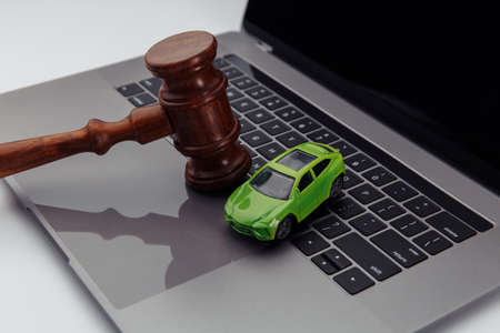Judge gavel and green toy car on laptop computer keyboard. Symbol of law, justice and online car auction.