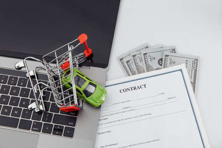 Purchase contract for a car with laptop, money and toy car in a shopping cart