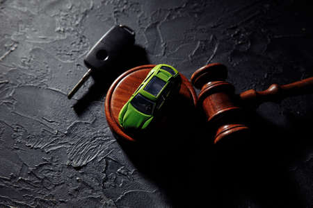 Wooden hammer and toy car with car keys. Insurance, court case
