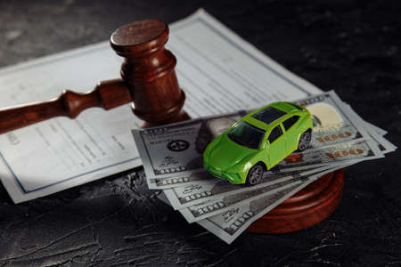 Toy car on dollar banknotes and wooden judge gavel with contract close-up 版權商用圖片