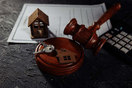 House, keys and wooden judges gavel on a table. Mortgage, bankruptcy or divorce concept