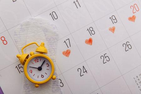 Females menstrual cycle concept. Menstrual calendar with sanitary pad and alarm clock close-up