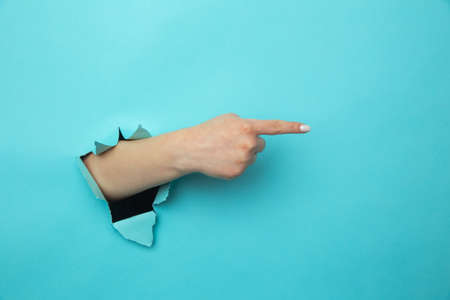Woman breaks arm through paper blue wall indicates on right at blank space gives advice