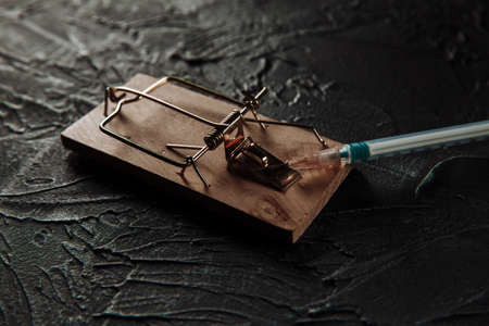 Mousetrap with a bait in the form of syringe. Addiction on drugs 版權商用圖片