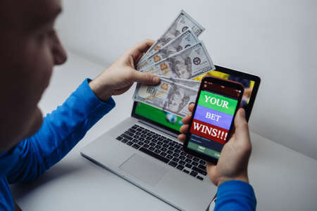 Lucky male winner at football betting with dollar bills and phone in hands. Betting and gambling concept