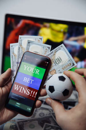 Smartphone with victory message and males hand with soccer ball. Sport and betting concept. Vertical image