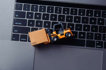Toy forklift with carton box on keyboard. Logistics and delivery concept