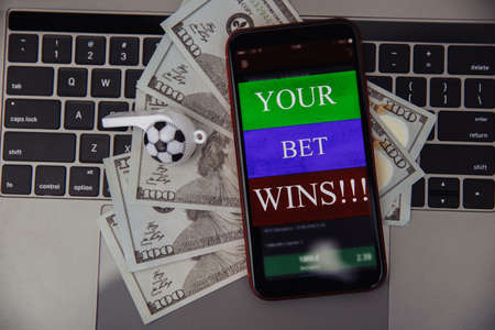Smartphone with online betting application, dollar bills and soccer whistle on a laptop. Gambling concept