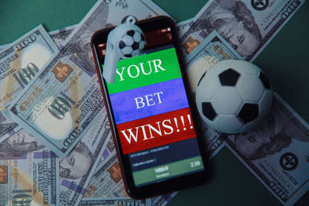 Football Business Concept. Ball and smartphone with bet application on dollar bills and green background. Gambling and bet concept