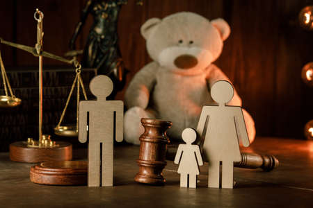 Wooden figures of family with teddy bear and gavel on a table. Divorce and alimony concept Banque d'images