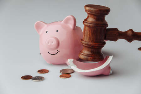 Broken pink piggy bank with coins and wooden judge gavel. Auction or bankruptcy concept