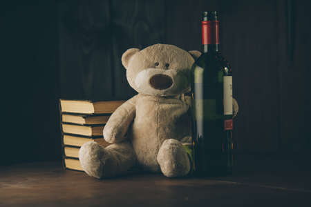Alcohol and family concept. Teddy bear as a symbol of childs safety and bottle with glass on a desk