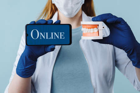 Portrait of beautiful female dentist posing in dental clinic holding smartphone with green screen and presenting mobile app or website to camera, copy space