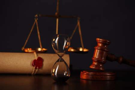 Wooden gavel, hourglass and stamp on testament and last will on wooden table. Notary public tools