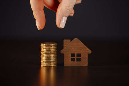 House model with stack of coins. Womans hand holding makes savings plans for housing, financial concept 版權商用圖片