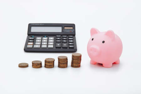 Finance Savings, save money for future investments and for emergency use concept. A pink piggybank, coin tower and calculator on white background