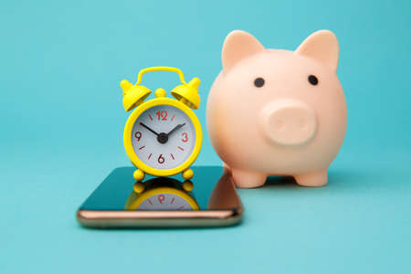 Smartphone, pink piggy bank and alarm clock isolated on blue background. Online shopping concept 版權商用圖片