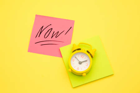 Sticker with handwriting the word NOW on alarm clock on yellow background with copy space using as stop procrastination, self discipline or motivation to complete task 版權商用圖片