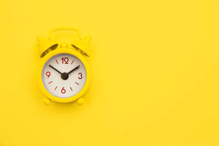 Yellow alarm clock Isolated on yellow trendy background. Rest hours time of life good morning night wake up awake concept. Space for text