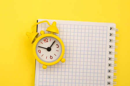 Yellow alarm clock and notebook on yellow background, empty space for text 版權商用圖片