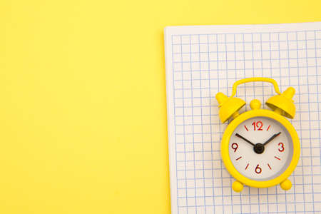Yellow alarm clock on notebook on yellow background, empty space for text